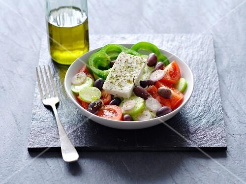 A Greek salad next to a bottle of olive oil