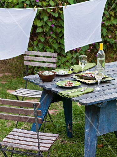 A vintage garden table laid for two with wine, salad and crackers