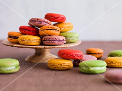 Various coloured macaroons on a cake stand and next to it