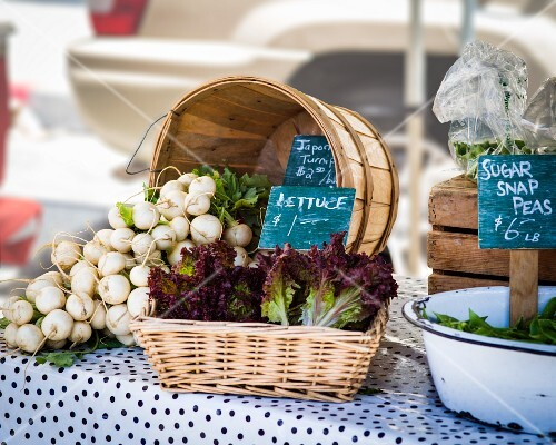 White radishes, lettuce and mange tout at a farmers market