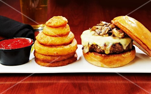 A cheeseburger with mushrooms served with onion rings and ketchup