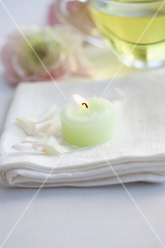 A burning candle on flower petals