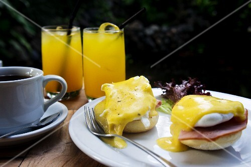 Eggs Benedict with ham served with coffee and juice on a table outside
