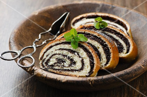 Four slices of poppyseed strudel in a wooden dish