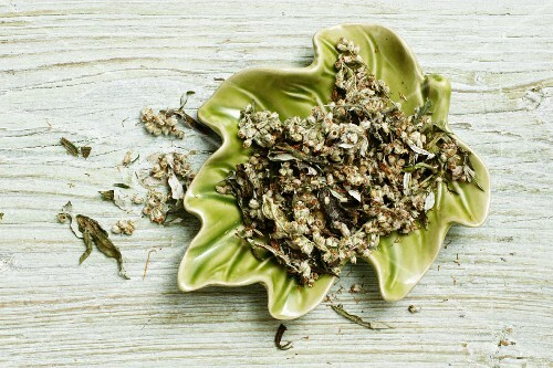 Dried mugwort with flowers in a leaf-shaped bowl