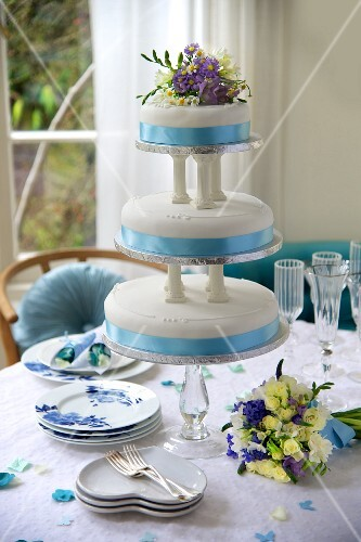 A three-tier, blue and white wedding cake decorated with flowers on a festively laid table