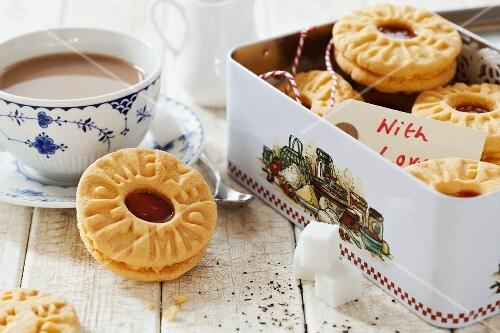 A tin of homemade jam and custard cream biscuits and a cup of tea