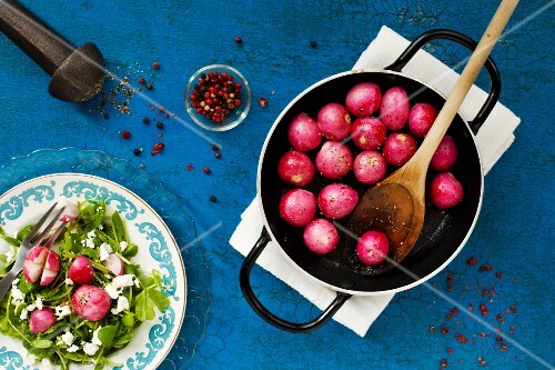 Caramelised radishes in a pan with a plate of feta and peas