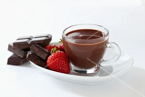 A small cup of thick Italian hot chocolate with strawberries and squares of dark chocolate