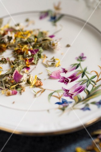 A mixture of herbs with various flowers on an old-fashioned plate