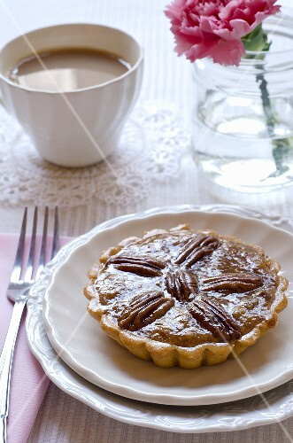 A mini pecan pie with a cup of coffee