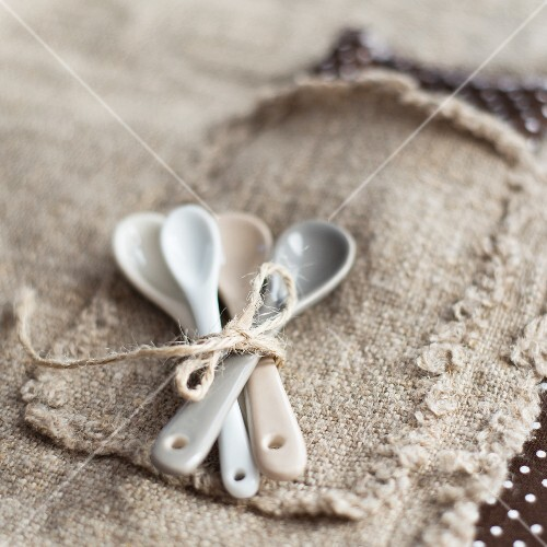 A bunch of small spoons tied together on a piece of jute