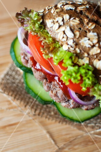 A wholemeal roll with minced beef, kethcup, gherkins, red onions, tomatoes and lollo rosso lettuce