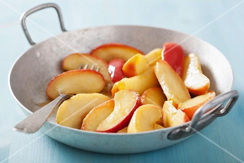 Caramelised apple slices in a frying pan