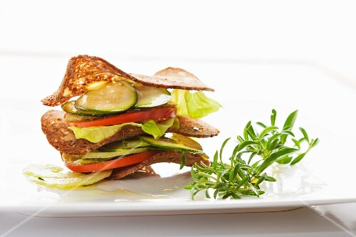 A stack of crisps, cucumber slices, tomatoes and lettuce