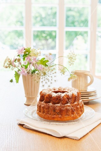 A Bundt cake with icing sugar on a table in front of a window
