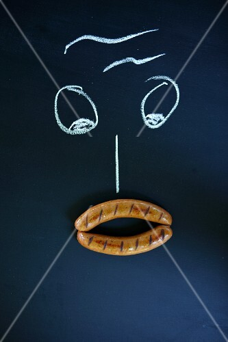 A face drawn with chalk with two sausages as a mouth