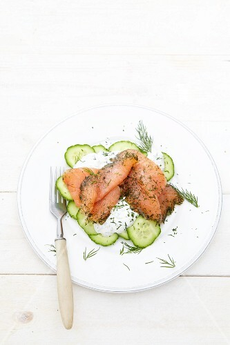 Smoked salmon on a bed of cucumber slices with sour cream and dill