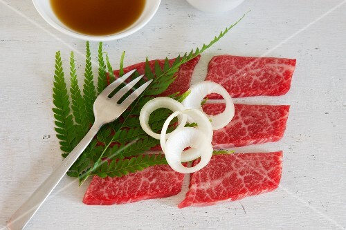 Wagyu garnished with onion rings and fern leaves