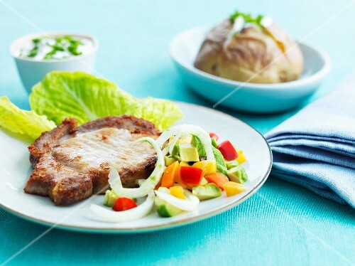 A pork chop served with salad and a baked potato