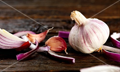A red onion and garlic on a wooden surface