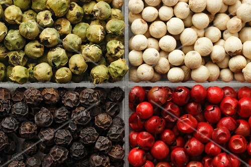 Different coloured peppercorns in a box