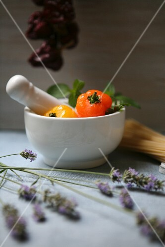 An arrangement featuring white mortar, lavender and fresh and dried peppers