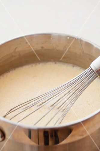 Melted butter with sugar and eggs in a pan with a whisk
