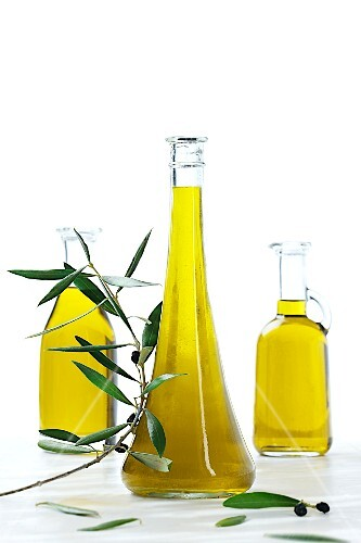 Three bottles of olive oil with an olive sprig