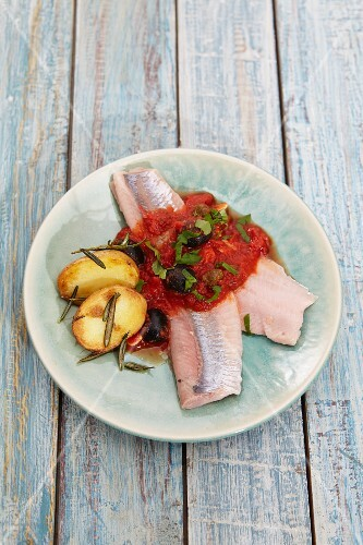 Soused herring fillets with tomato sauce, olives and rosemary potatoes