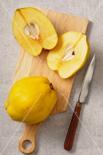 Quinces, whole and halved, on a chopping board