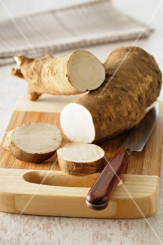 Horseradish, sliced, on a chopping board