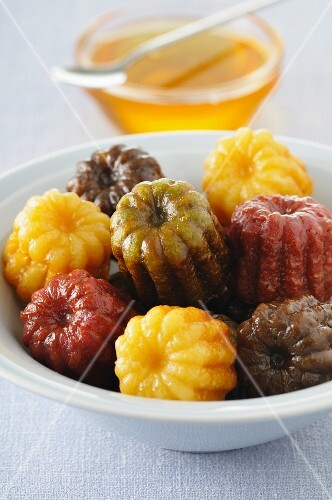 Various coloured canneles with honey
