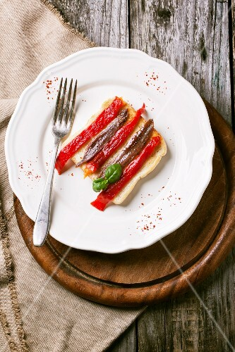 Toast topped with grilled pepper and anchovies on a plate