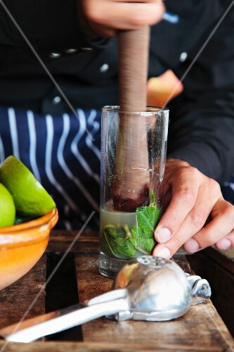 A mojito being made (mint being crushed with sugar and lemon juice)