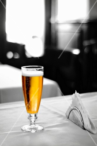 A glass of lager on a table in an Italian bar