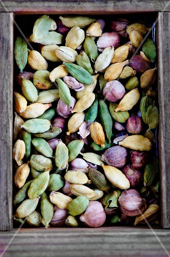 Various types of cardamom pods in a wooden box