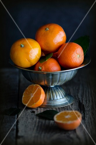 Fresh clementines in a metal bowl on a wooden surface