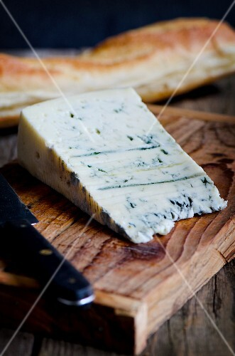 A slice of Gorgonzola on a wooden board with a baguette and a knife
