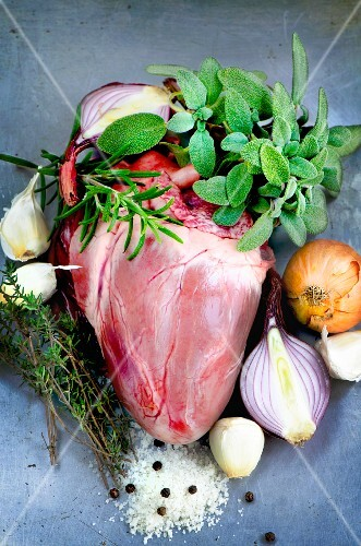 A whole pig's heart surrounded by sage, rosemary, thyme, onions, garlic, salt and pepper