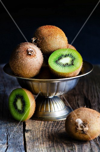 Kiwis, whole and halved, in a metal bowl