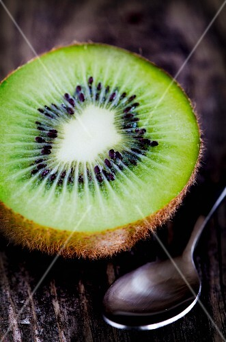 Half a kiwi and a spoon on a wooden surface