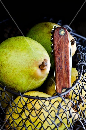 Pears in a wire basket with a knife