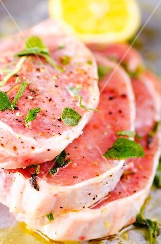 Raw pork chops marinated in olive oil, sage, lemon juice, salt and pepper