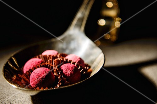 Pink truffle pralines on a spoon
