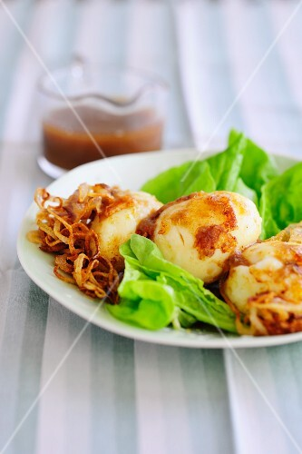 Eggs with onion sauce on a bed of salad