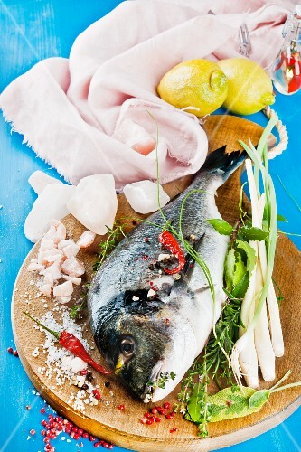 Sea bream on a wooden board with Himalayan salt and various herbs