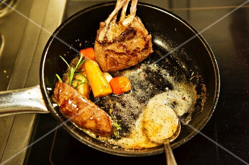 Venison with vegetables and herbs being fried in a pan