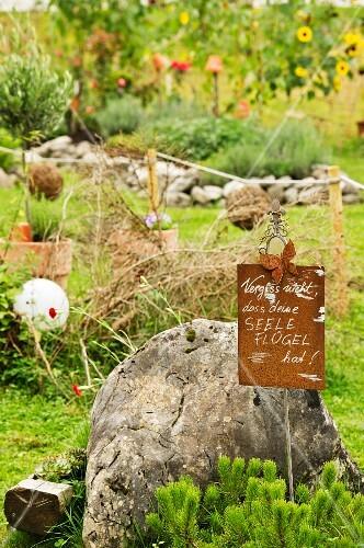 A boulder and a sign in a garden