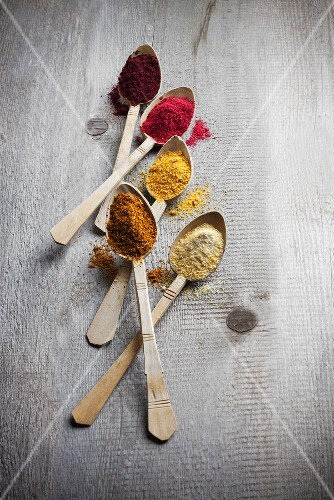 Five different types of fruit powder on wooden spoons